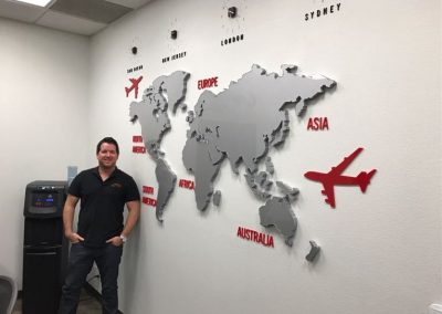 Ryan Silva with at the office with world clock backdrop